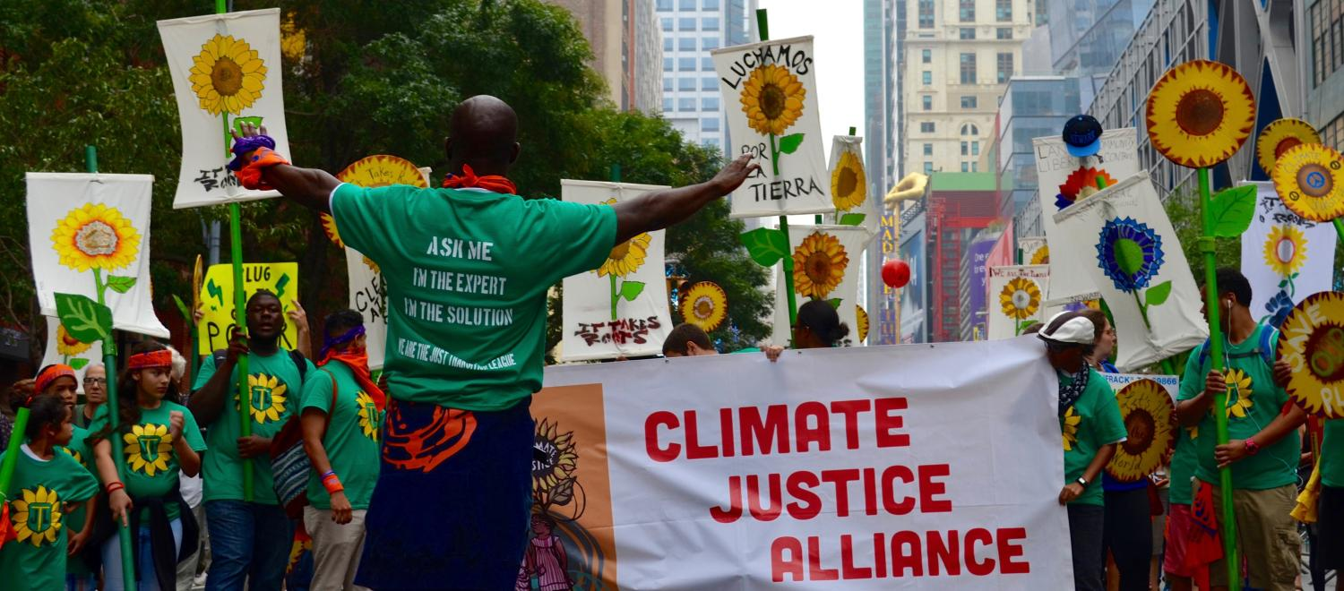 "A group marches in the Peoples Climate March holding a banner ""Climate Justice Alliance"""