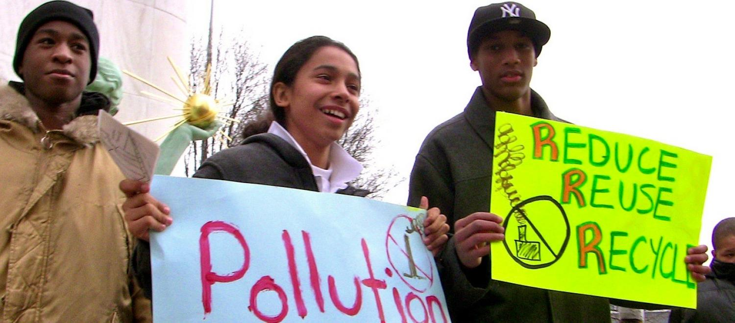 Three youth holds signs at a demonstration against a waste incinerator in Detroit
