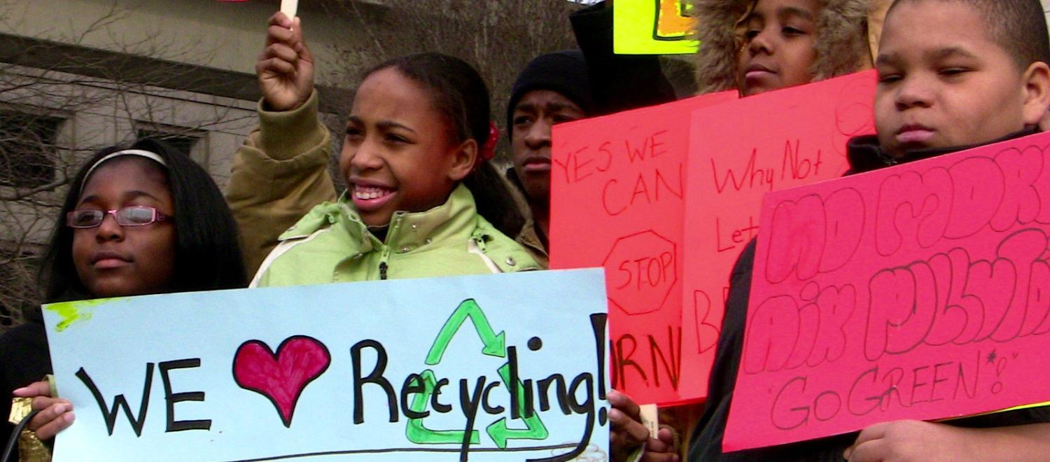 Youth holds signs at a demonstration against a waste incinerator in Detroit