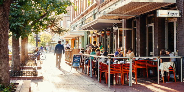 A picture of a man walking by a restaurant on Pearl Street in Boulder, CO