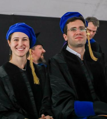 Two graduates at their ceremony