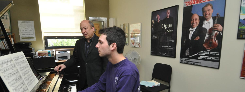 man sitting at piano playing, teacher behind him