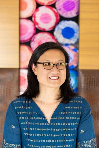 Jennifer Ho facing front smiling, colorful backdrop
