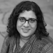 woman facing front smiling glasses, black and white photo