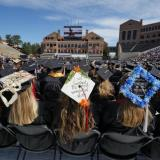 """A trio of decorated mortar boards celebrate the graduates' successes. The featured mortar board says, """"I just finished the most wonderful story."""""""