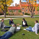 People sit in a circle on a campus lawn