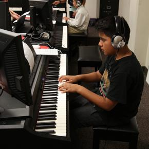 An elementary student practices during Piano for Dreamers class