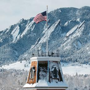 The flag flies atop Old Main against the backdrop of the snowy Flatirons