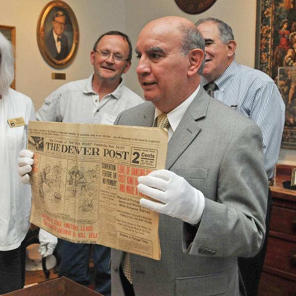 Chancellor DiStefano shows a 100-year-old issue of the Denver Post newspaper from the Macky Auditorium time capsule.