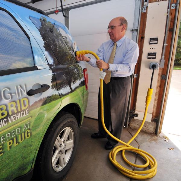 Phil DiStefano plugs in his hybrid vehicle to show the interface his residence has with the Xcel Smart Grid program.