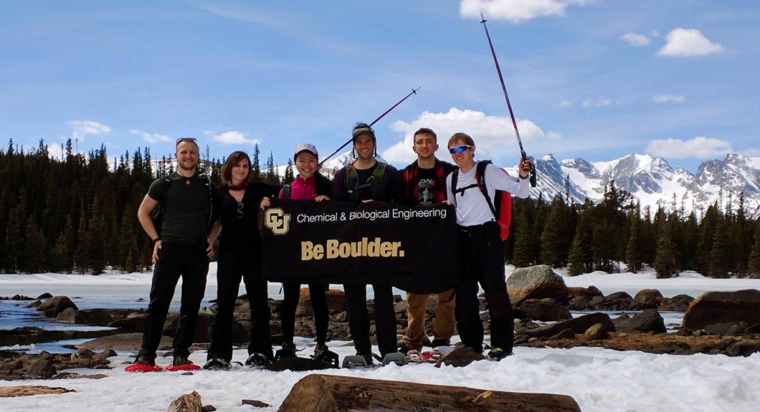 AIChE chapter members on a hiking trip with a CU Boulder banner