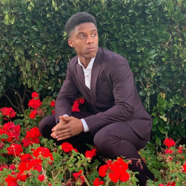 Nadir Shakir in suit kneeling near red flowers
