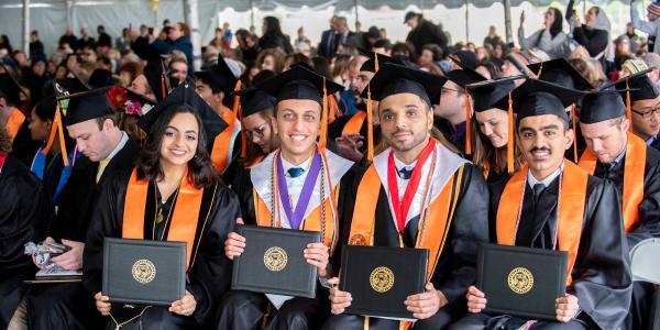 Graduates pose with their diplomas