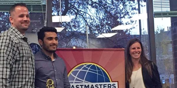 Hashim Al Hajji stands with Toastmasters International representatives with trophy.