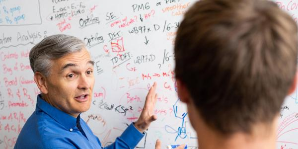 Charles Musgrave discusses some notes on a whiteboard with a student