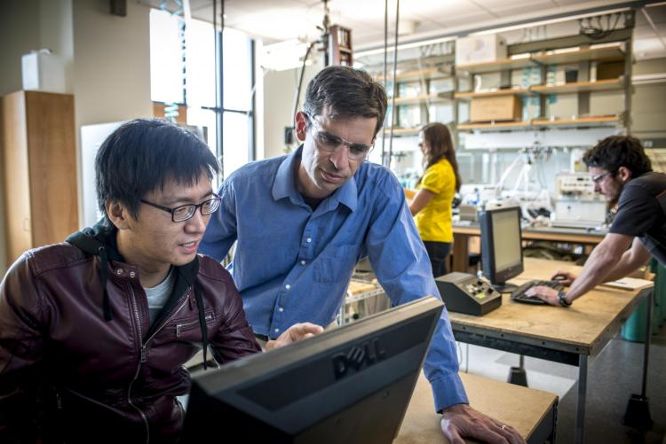 Professor Will Medlin works at a computer with a graduate student.