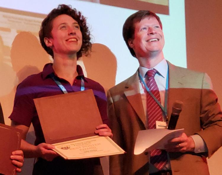 Julia Hartig accepts an award on stage at AIChe conference