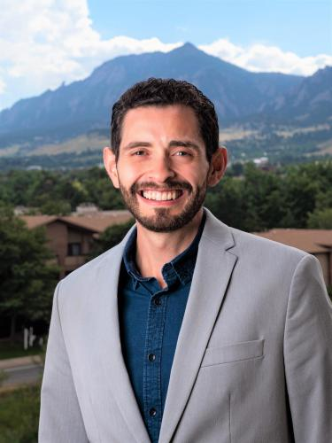 Brian Aguado in grey suit with Flatirons background