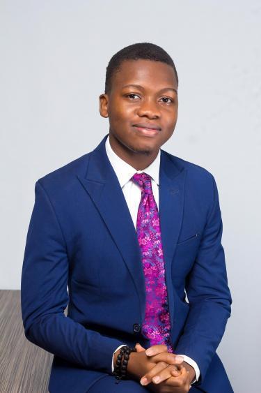 Dami Akinneye in blue suit and purple tie