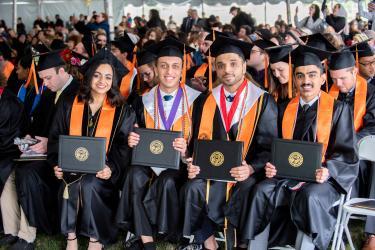 Graduates display their diploma cases