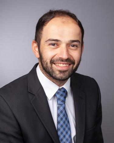 Ehsan Keyvani in black suit with white shirt and blue tie