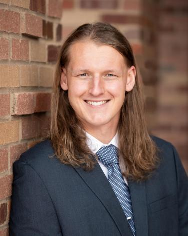 Todd Whittaker in suit in front of brick background