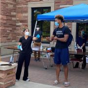 Volunteers test students at a collection station outside of the Athletics Department