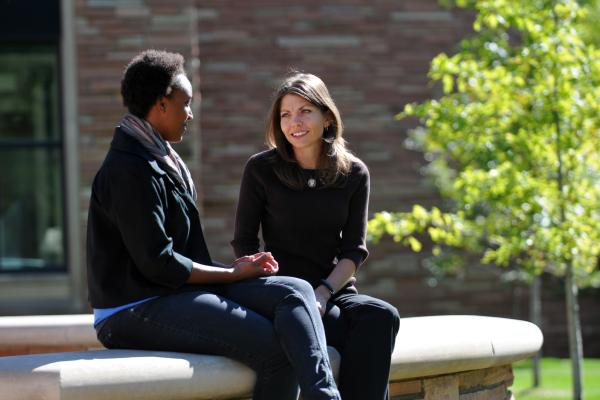 Student and advisor chatting outdoors on CU's campus