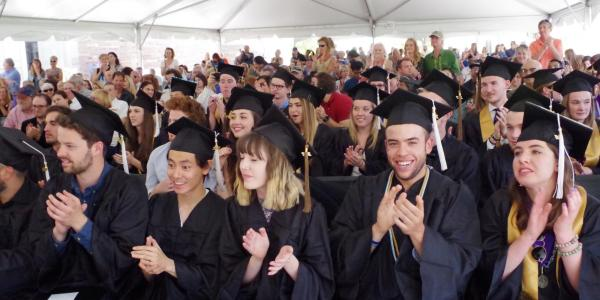 Large group of graduating students clapping