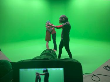 Kelly Sears in the Green Studio directing dancers movement in the green screen space in front of the camera.
