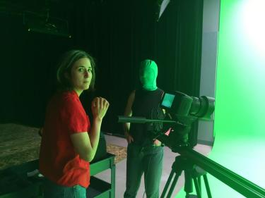 Laura directs Graduate dancer Madison Palffy who is wearing a green screen mask and they are both standing nearby a camera and the green screen.