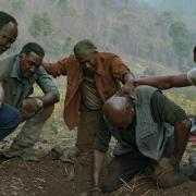 "Actors Isiah Whitlock Jr, Norm Lewis, Clarke Peters, Delroy Lindo, and Jonathan Majors, playing Vietnam War veterans in ""Da 5 Bloods."" The actors are consoling each other on the ground in a forrest"