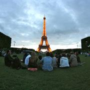 Group of students sitting on the ground near the Eiffel Tower.