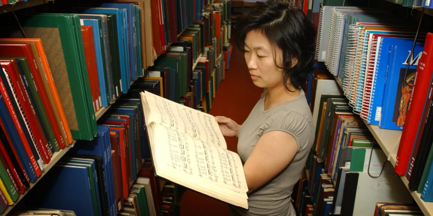 woman reading music book in library stacks