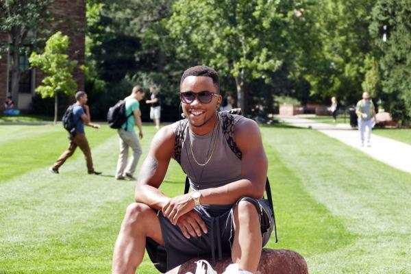 Young man sitting on CU Boulder's campus