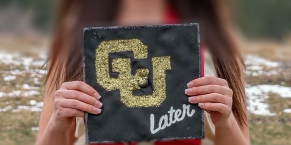 student holding mortarboard with cu later written