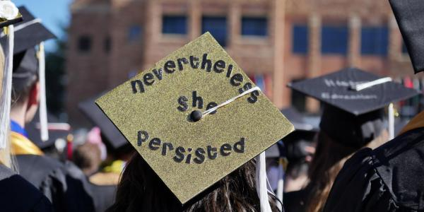 "CU commencement student with mortarboard that says ""but she persisted"""