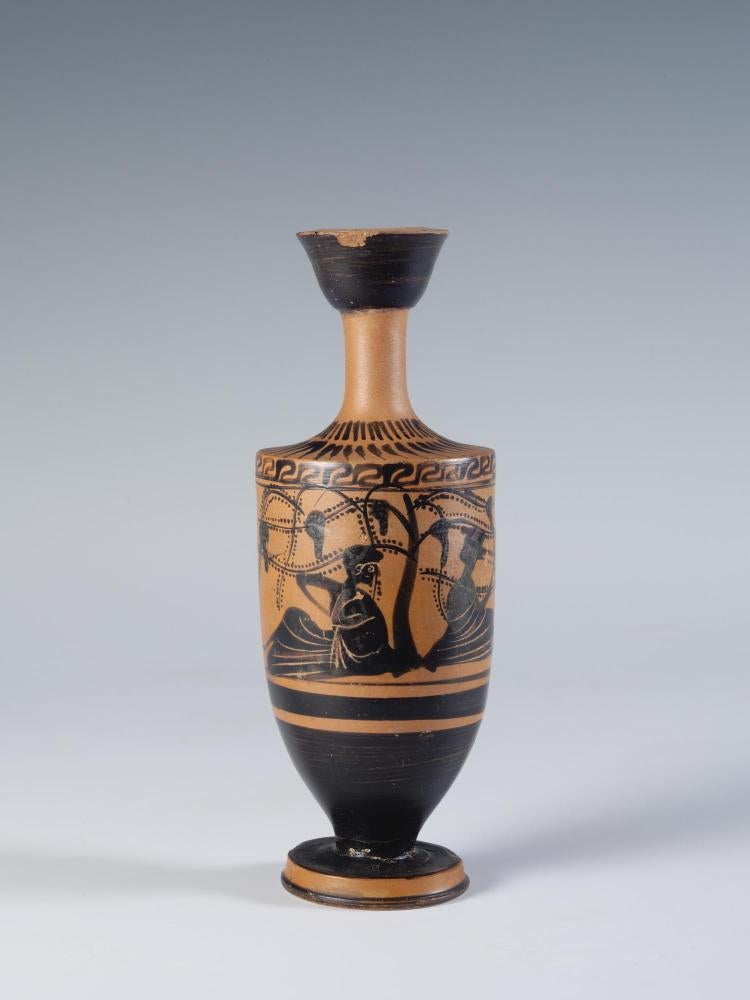 Photograph of a black-figure lekythos showing two human figures reclining beneath a productive grape arbor, from the side against a neutral gray background.