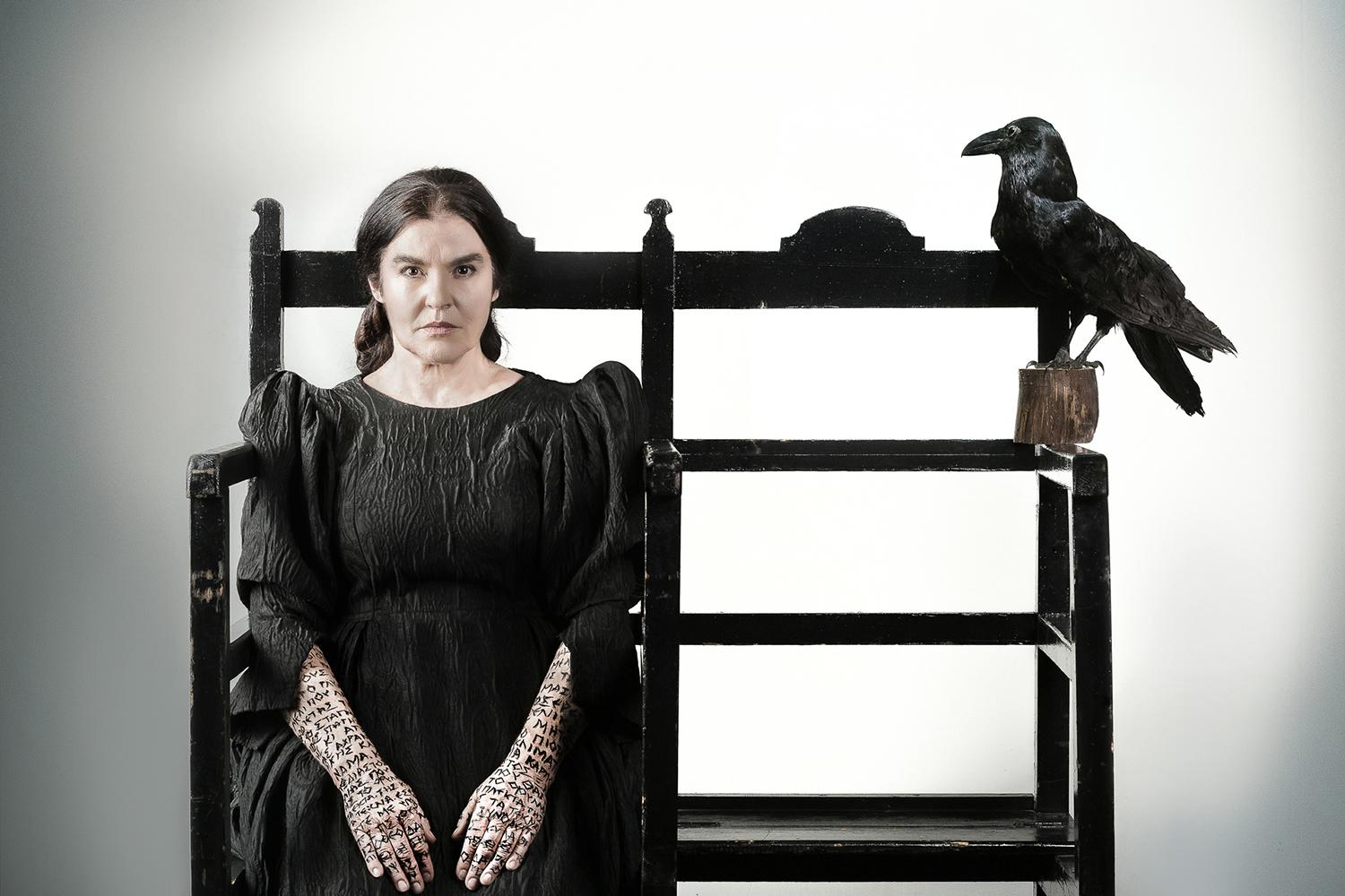 woman sitting on chair with raven