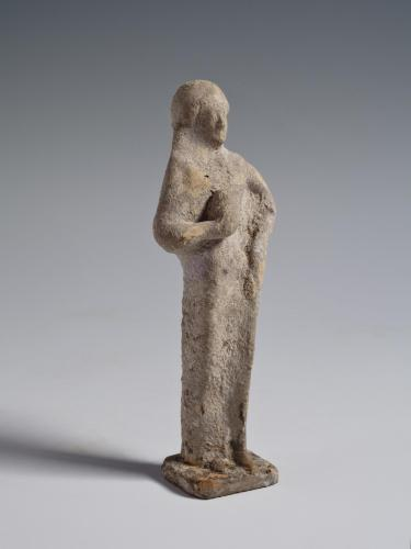 Photograph of terracotta female figurine, facing slightly to the viewer's right, against neutral gray background.