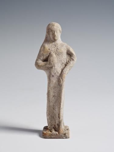 Photograph of terracotta female figurine, frontal, against neutral gray background.
