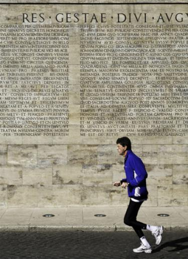 Man running past ancient Latin inscribed on a wall