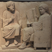 carving of a greek tutor teaching a pupil, Carole Raddato from FRANKFURT, Germany, CC BY-SA 2.0 <https://creativecommons.org/licenses/by-sa/2.0>, via Wikimedia Commons
