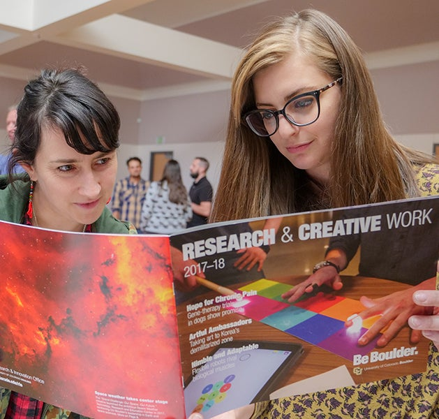 Students look through a magazine at the Research Fair.