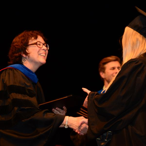 Professor shakes hand with graduating student