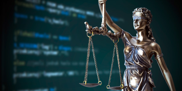 Blindfolded Lady Justice against a computer screen
