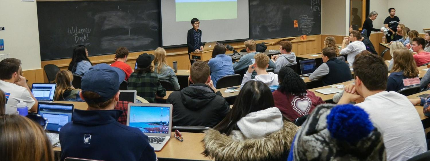 A faculty member lectures to a classroom full of undergraduate students