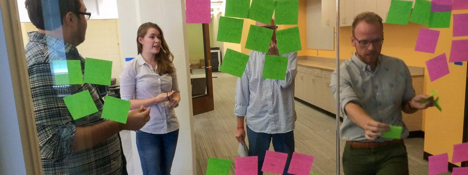 Three men and one woman put sticky notes on a glass wall.