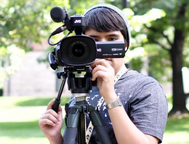 The Pathways to Excellence program offers first-generation and underrepresented students the opportunity to gain handson training with technology and media creation. Senior Instructor Ruth Hickerson is the program's new director. Above, student Josh Bustillos works with a camera during the 2017 summer program. Photo by senior journalism student Katie Pickrell.