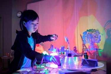 A girl stands at a table arranging objects.